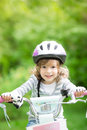 Happy kid sitting on the bike outdoors in spring park Stock Photography