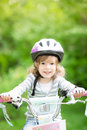 Happy kid sitting on the bike outdoors in spring park Royalty Free Stock Photos