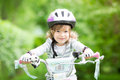 Happy kid sitting on the bike outdoors in spring park Stock Photo