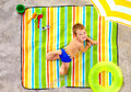 Happy kid sunbathing on colorful beach cute summer Stock Photos