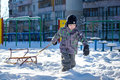 Happy kid walking outdoors in winter city drags his sled. child smiling and having fun. Royalty Free Stock Photo