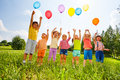Happy kids with balloons and arms up in the sky green field Royalty Free Stock Photos