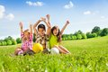 Happy kids with balls and lifted hands portrait of three boy girls sitting in the grass in park holding sport Royalty Free Stock Photos