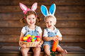 Happy kids boy and girl dressed as Easter bunnies with basket of Royalty Free Stock Photo