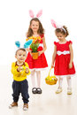 Happy kids with bunny ears toddler boy in front of camera and his siters in background wearing all and holding easter basket eggs Royalty Free Stock Photos
