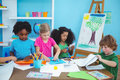 Happy kids doing arts and crafts together at their desk Stock Images
