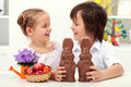 Happy kids at easter time with large chocolate bunnies laughing and colorful eggs Stock Photo