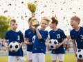 Happy kids in elementary school sports team celebrating soccer succes in tournament final game Royalty Free Stock Photo