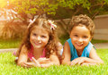 Happy kids on green grass two lying down brother and sister enjoying warm sun light beat friends summer holiday Royalty Free Stock Photography