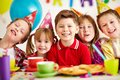 Happy kids group of adorable looking at camera while having fun at birthday party Royalty Free Stock Photos