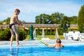 Happy kids having fun playing in water park pool Stock Image