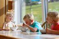 Happy kids having healthy breakfast in the kitchen group of two brothers and little sister sitting at wooden table sunny with Stock Photo