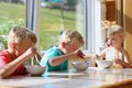 Happy kids having healthy breakfast in the kitchen group of two brothers and little sister sitting at wooden table sunny with Royalty Free Stock Photo