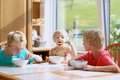 Happy kids having healthy breakfast in the kitchen group of two brothers and little sister sitting at wooden table sunny with Royalty Free Stock Photos
