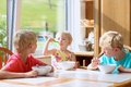 Happy kids having healthy breakfast in the kitchen group of two brothers and little sister sitting at wooden table sunny with Stock Photos