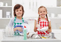 Happy kids helping in the kitchen doing dishes Royalty Free Stock Photos
