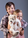 Happy kids holding their new pet a small fluffy dog Royalty Free Stock Image