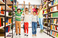 Happy kids jumping with hands up in the library and standing between bookshelves Royalty Free Stock Images
