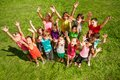 Happy kids large group of boys and girls with lifted hands about years old standing on the green grass top view Royalty Free Stock Images