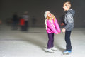 Happy kids laughing at ice rink outdoor, ice skating Royalty Free Stock Photo