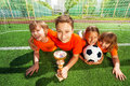 Happy kids laying on grass with golden goblet and football together Royalty Free Stock Photography