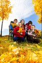 Happy kids like autumn five boy and girls with maple leaves in the park under the trees low angle Stock Photo
