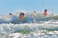 Happy kids playing on beach in water against the waves Stock Photography