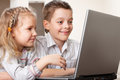 Happy kids playing laptop at home Stock Photography