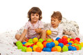 Happy kids playing with many balls in bed Royalty Free Stock Images