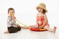 Happy kids playing on toy music instrument little boy singing to microphone over white background Stock Image
