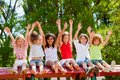 Happy kids raising hands outdoors group of children together in park Royalty Free Stock Photography
