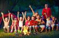 Happy kids singing songs around camp fire group of having fun Stock Image