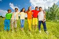 Happy kids standing in a row straight and hug shoulders of each other outside Royalty Free Stock Photo