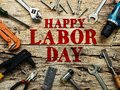 Happy Labor day text in red color on wooden background with construction repair tools.