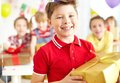 Happy lad joyful boy with giftbox looking at camera with his friends on background Stock Image