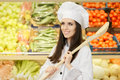 Happy lady chef with big spoon shopping for vegetables portrait of a young female cook in a grocery store Stock Photography