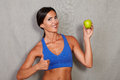 Happy lady with thumb up showing apple sign while and wearing fitness sport wear against grey texture background Stock Photos
