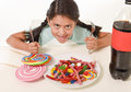Happy Latin female child eating dish full of candy and gummies with fork and knife and big cola bottle in sugar abuse Royalty Free Stock Photo