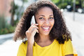 Happy latin woman with curly hair at phone in summer Royalty Free Stock Photo