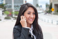 Happy latin woman talking at phone in the city Royalty Free Stock Photo