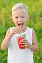 Happy laughing boy holding drinking a glass of red fresh juice watermelon. Summer time. Healthy lifestyle Royalty Free Stock Photo