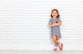 Happy laughing child girl near brick empty wall Royalty Free Stock Photo