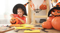 Happy laughing child girl in a witches hat eats sweets in Hallow Royalty Free Stock Photo
