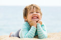Happy laughing girl laying on sand beach Royalty Free Stock Photo