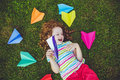 Happy laughing girl throwing paper airplane in green grass at su Royalty Free Stock Photo