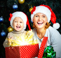 Happy and laughing mother with little child hold the box with gi gifts for christmas indoors Royalty Free Stock Photography