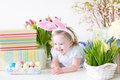 Happy laughing toddler girl with eggs spring flowers Royalty Free Stock Photo