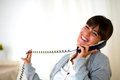 Happy laughing woman conversing on phone at home Royalty Free Stock Photo
