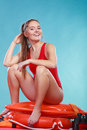 Happy lifeguard woman sitting on rescue ring buoy. Royalty Free Stock Photo