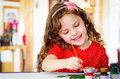 Happy little artistic girl painting Royalty Free Stock Photo